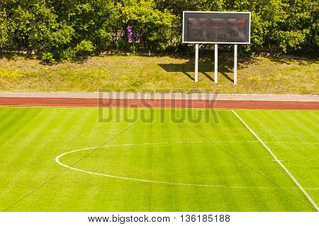 Football field with fresh green grass and score board