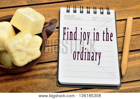 Text Find joy in the ordinary on notebook