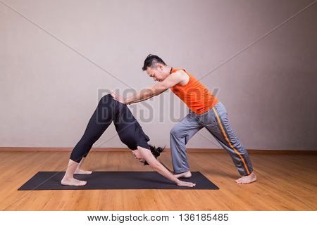 Yoga Instructor Guiding Student Perform Downward Facing Dog Pose