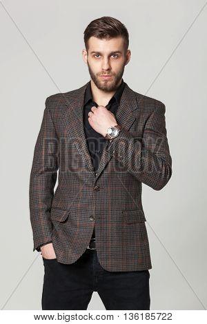 Studio Portrait Of Handsome Elegant Young Man In Brown Jacket Posing.