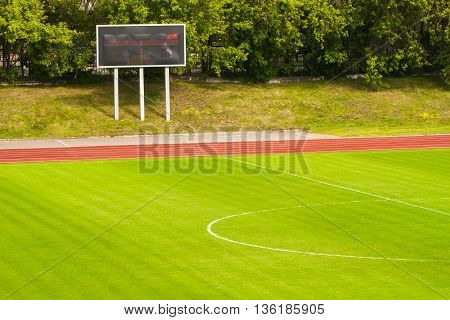 Football field with fresh green grass and score board, summer