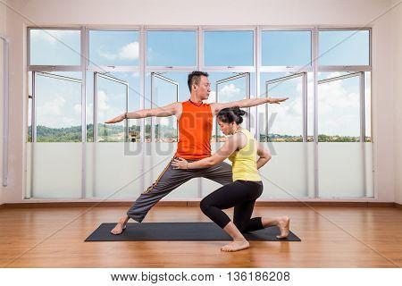 Yoga Instructor Correcting Student Performing Warrior 2 Or Virabhadrasana 2