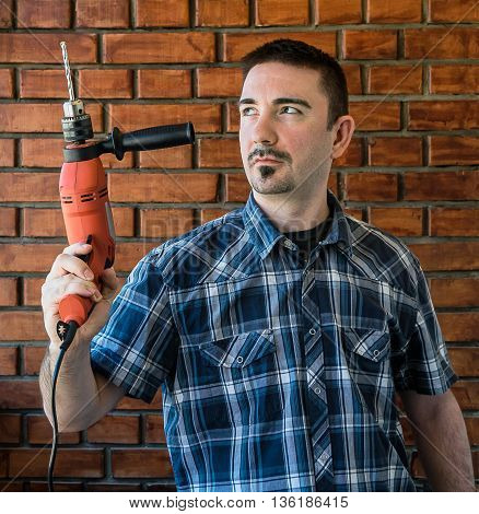 Young man in plaid shirt with trim beard in his 30s holding a red electric drill on a red brick background background