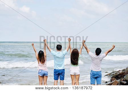 Rear view of young people standing at the beach and holding hands