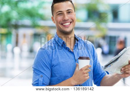 Man holding newspaper and coffee