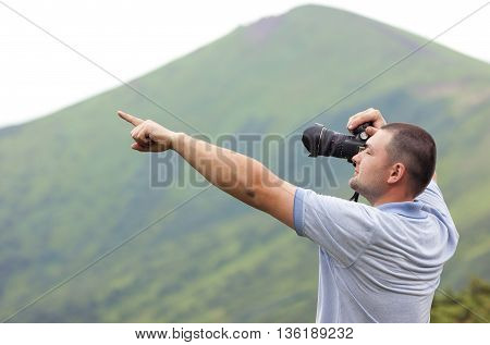 Photographer with a camera taking picture of mountains pointing with finger