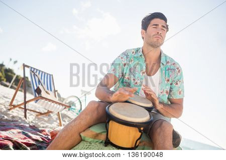 Man playing the drums at the beach