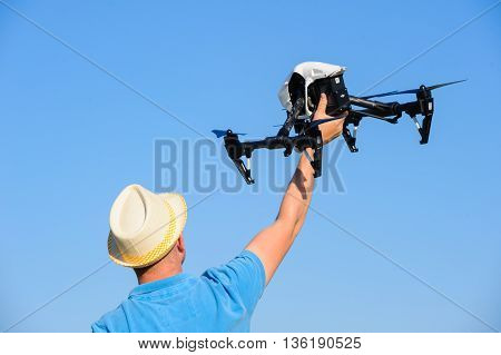 Man in hat holding drone in hand against the blue sky