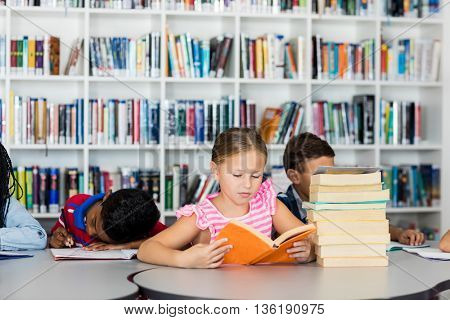 A little girl reading books in library