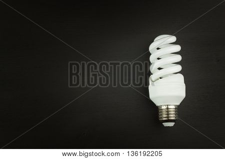 Energy saving lamp on black wooden background. Sales of light bulbs. Advertising for energy-saving bulbs. Place for your text.