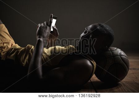 Portrait of basketball player lying and using his smartphone on a gym
