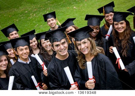 group of graduation students in the park looking happy
