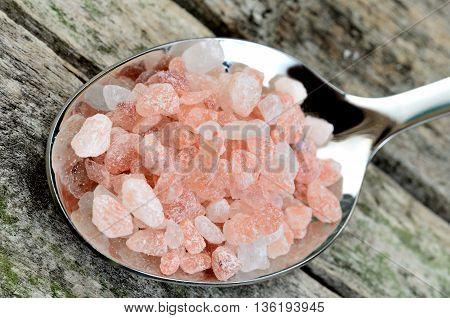 Pink salt in spoon on rustic table