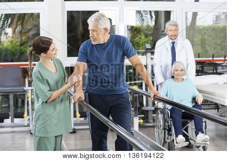 Man Looking At Physiotherapist While Doctor Pushing Woman In Whe