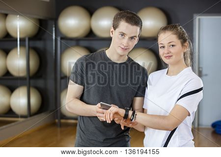 Young Friends Using Mobile Phone And Smart Watch In Gym