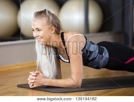 Woman Performing Plank Exercise In Gym