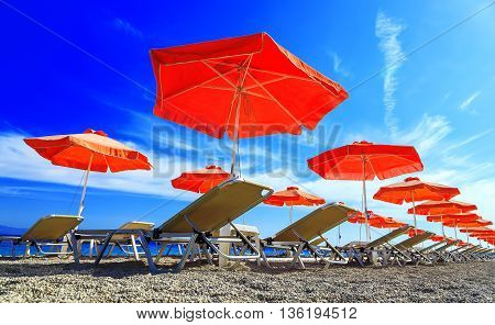 Umbrella bed deck on tropical beach with blue sky