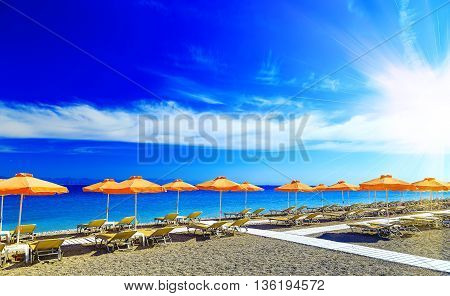 Greece, reed umbrellas and yellow sunbeds on pebble beach at Aegean Sea of Rhodes, Greece
