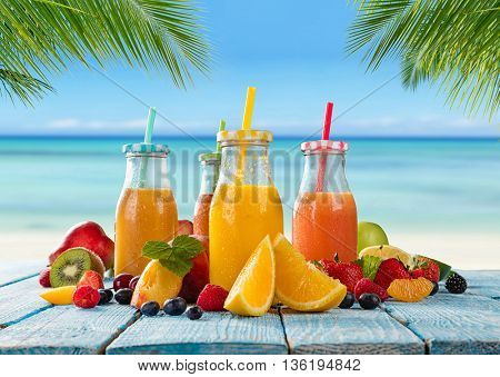 Fresh glasses of juice with fruit mix placed on the beach on wooden planks. Concept of healthy drinks, antioxidants and summer cocktails.