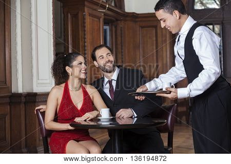Happy Waiter Serving Coffee To Tango Couple In Restaurant