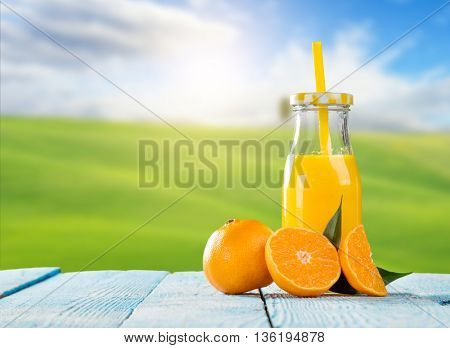 Fresh glass of juice with mandarin placed on wooden planks. blur garden on background. Concept of healthy drinking, antioxidants and summer cocktails.