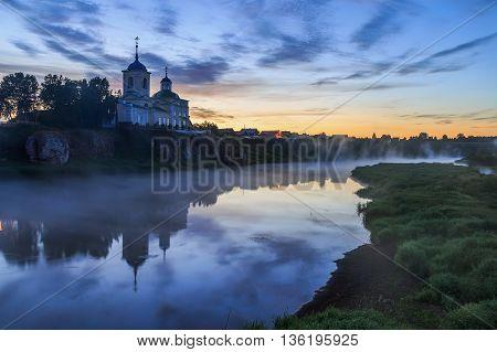 Russian orthodox monastery. Fog over river near the cliff and church. Ural, Chusovaya.