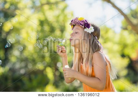 Cute young girl blowing bubbles through bubble wand in park