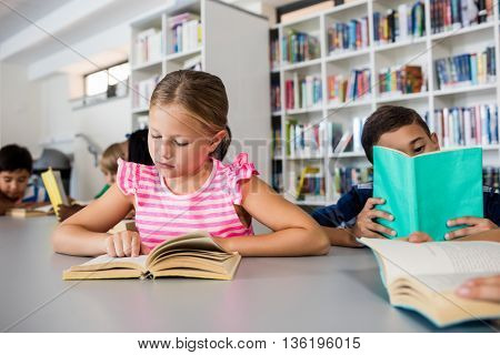 Little children are reading books in library