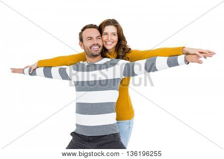 Young couple standing with arms outstretched on white background