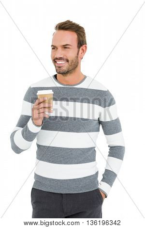 Happy young man in winter wear holding disposable coffee cup on white background