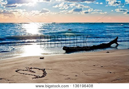 a heart waiting for you on the beach by the sea lit by the sunset