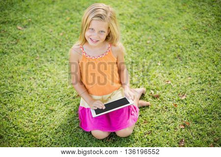 Portrait of cute young girl sitting and using digital tablet in park