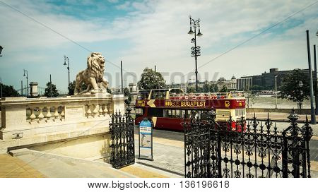 Budapest, Hungary - July 07, 2015: lion statue and gate of Buda castle at lower part with touristic bus on the street