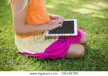 Young girl sitting and using digital tablet in park