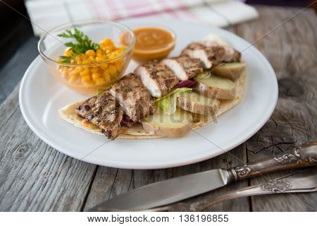 Grilled chicken breast served with sweet corn and potatoes
