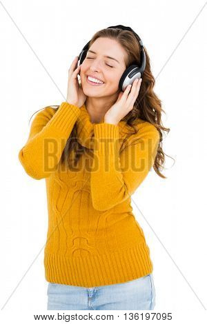 Young woman listening to music on headphones on white background