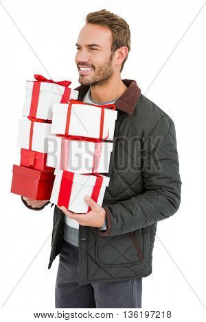 Happy young man holding gifts on white background