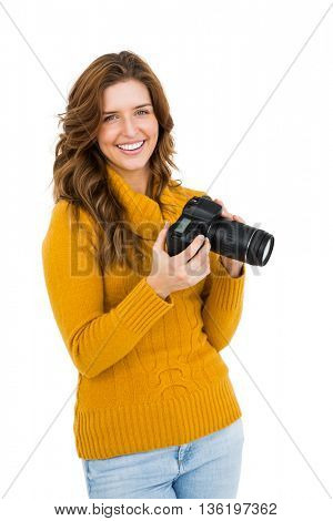Portrait of happy young woman using camera on white background