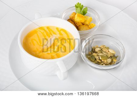 Creamy pumpkin soup served with croutons and sunflower seeds