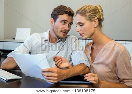 Young colleagues discussing by desk in office