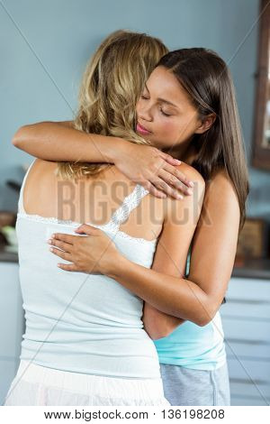 Beautiful young female friends embracing at home