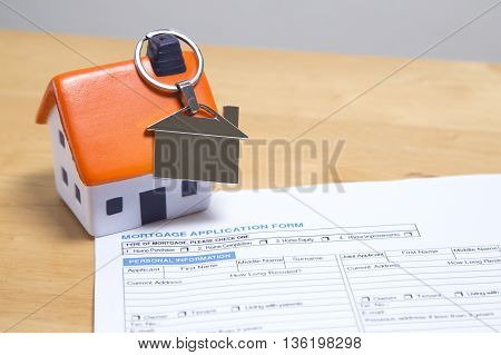 Foam house with silver key ring on chimney sitting on mortgage application form