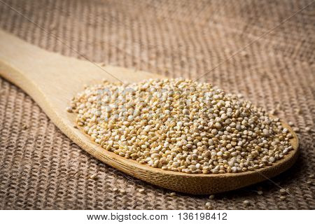 Heap of quinoa on wooden spoon and linen background closeup.