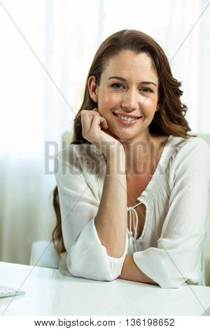 Portrait of businesswoman with hand on chin at desk in office