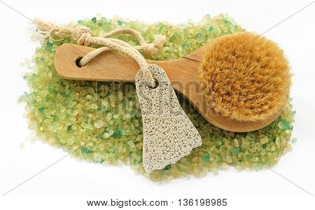 background of large salt crystals colorful yellow green bath with juniper spa pumice in the form of a foot with a rope brush massage