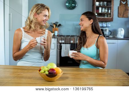 Happy female friends standing in kitchen at home