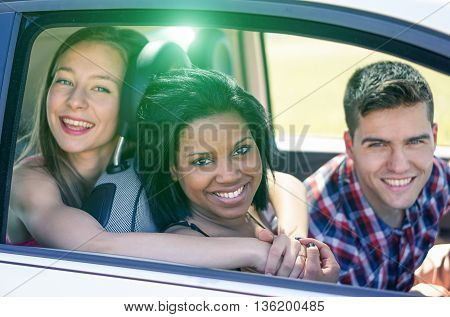 Multiracial friends driving to vacation in the car - Happy mixed race in an automobile with back lighting - Multi ethnic friendship concept - Soft focus on black girls with soft warm filter