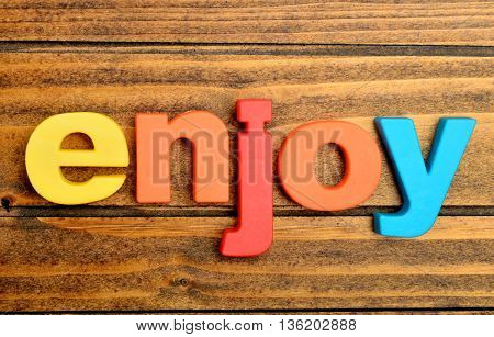 The word Enjoy on wooden table closeup