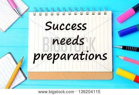 The words Success needs preparations on notebook