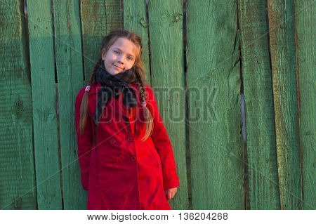 girl in red raincoat near green wooden fence by evening